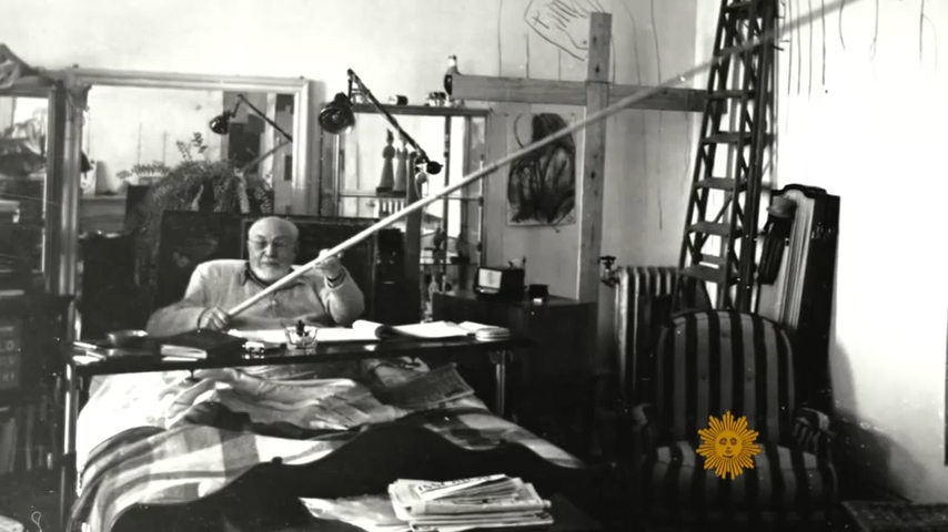 Henri Matissein bed at studio composing cutout pieces with long stick